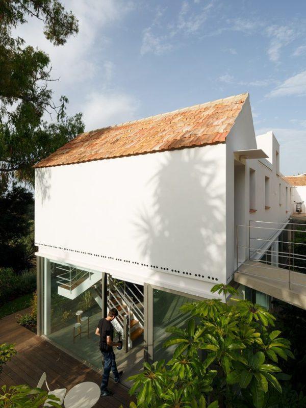 Pasarela de entrada al apartamento y doble altura sobre el patio tropical