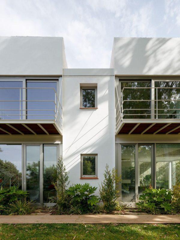Fachada sur de la vivienda con grandes ventanas