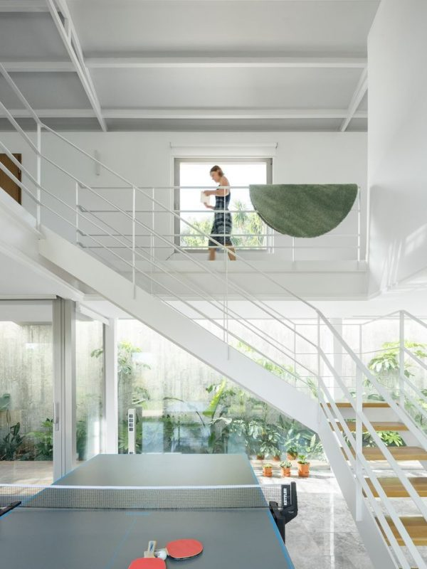 Salon de doble altura con tenis de mesa y escalera metálica