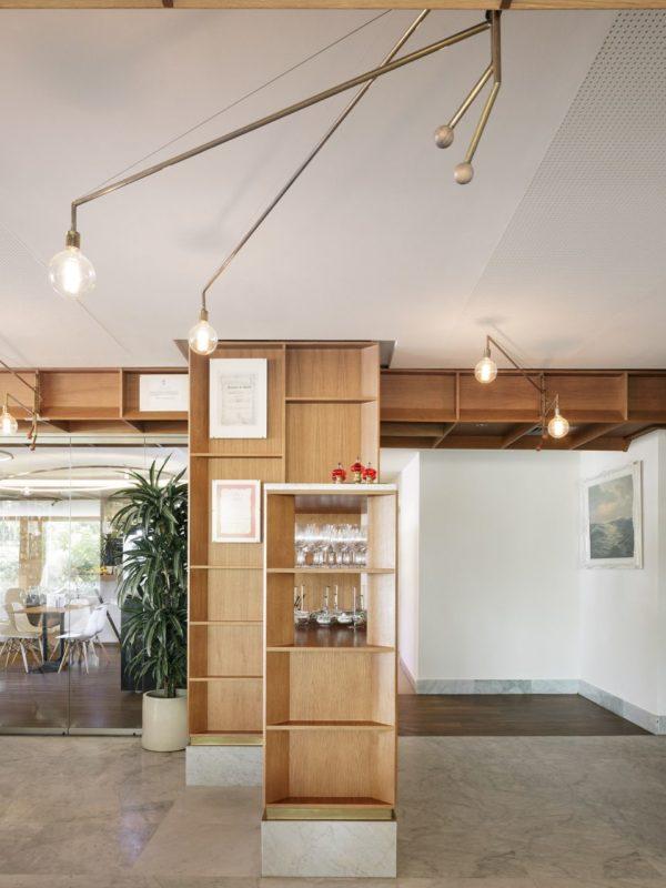 Detalle de pilar y mueble de madera con lamparas de laton